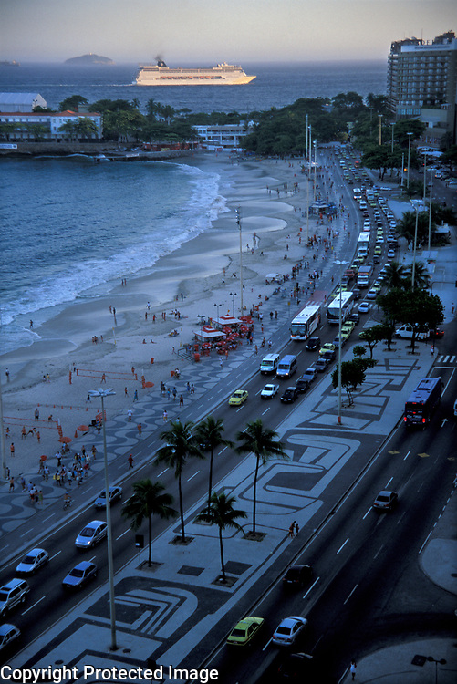 Cruise ship passing past Copacabana Beach already in shade in late afternon, Rio de Janeiro, Brazil