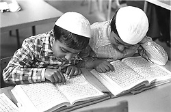 Two young boys sitting at desk in school classroom reading the Koran,