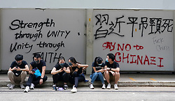 Hong Kong. 1 October 2019. After a peaceful march through Hong Kong Island by an estimated 100,000 pro democracy supporters, violent flared up at Tamar, Admiralty and moved through Wanchai district. Police used teargas and baton rounds and water cannon. Hard core group lit fires, threw bricks and Molotov cocktails at police. Violence continues into evening. Protestors rest beside vandalised tram stop. Iain Masterton/Alamy Live News.