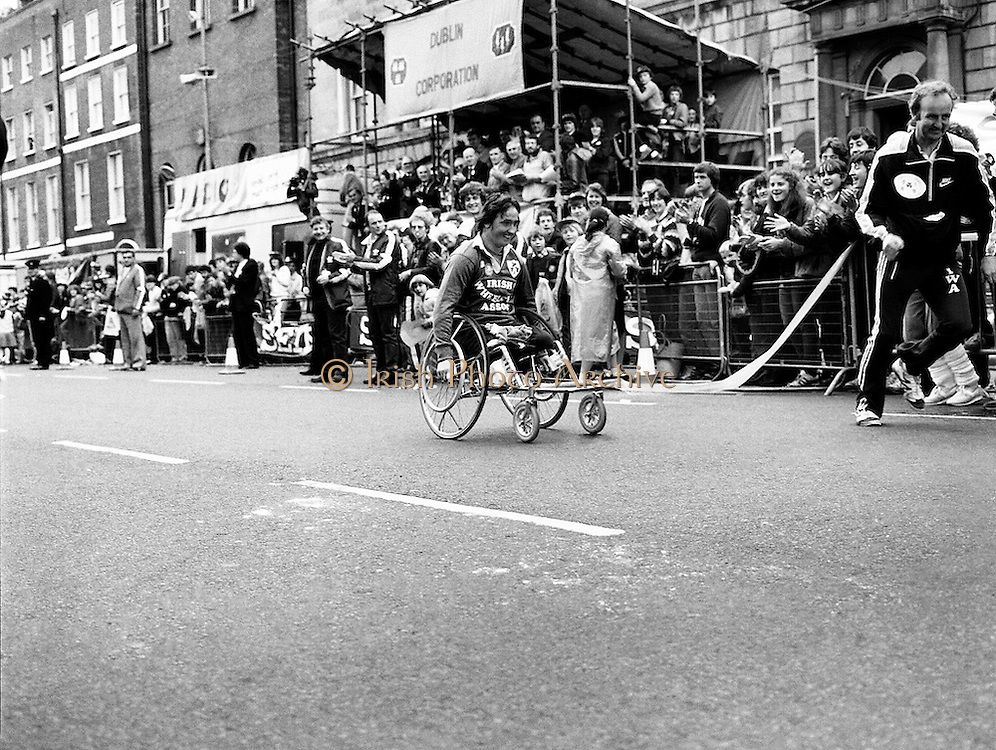 The finish of the Dublin City Marathon, at St Stephen's Green. Using just hand power, Michael O'Rourke approaches the finish line, cheered on by the crowd, to win the wheelchair event.<br /> 25 October 1982