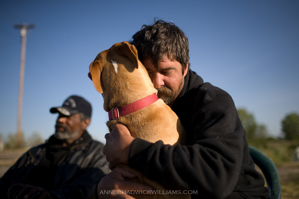 A homeless man hugs his dog as he is evicted from tent city in Sacramento, CA.