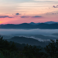 Sun rising behind Smoky Mountains and foggy valleys