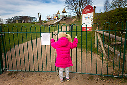 © Licensed to London News Pictures. 23/03/2020. Leeds UK. 4 year old Scarlet stands at the locked gates of Temple Newsam Park playground as Leeds City Council closed all the playgrounds in council parks this morning in a bid to limit the spread of Coronavirus. Photo credit: Andrew McCaren/LNP