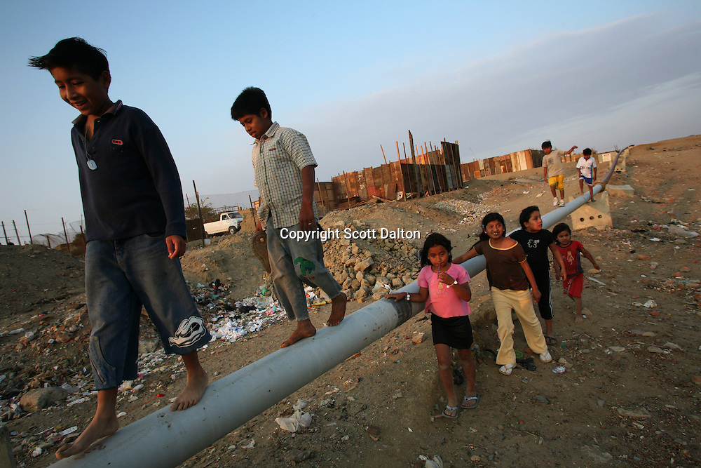 A group of children play around and walk on an oil pipeline that runs through their poor barrio in Talara, on Peru's northern coast on November 11, 2007. Talara is one of Peru's main oil producing regions and the Chinese company SAPET has an oil field in the region. (Photo/Scott Dalton)