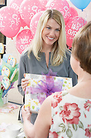 Woman Receiving a Gift at a Baby Shower