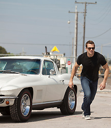 man on the go by a parked Corvette in Florida