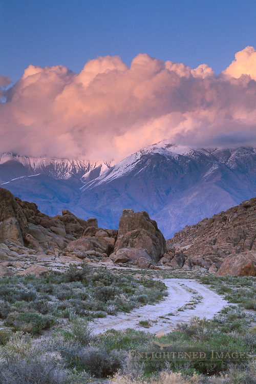 Alpenglow on storm clouds over mountains at sunset over dirt road in the Alabama Hills, Lone Pine, Eastern Sierra, California