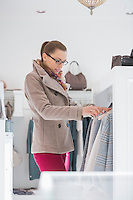 Young woman choosing sweater in store