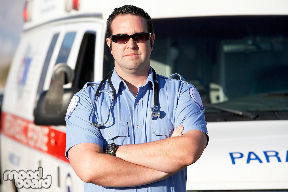 Paramedic worker standing in front of ambulance (portrait)