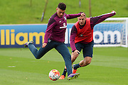 England midfielder Alex Oxlade-Chamberlain skips the ball past defender Phil Jagielka during the England Training Session at St George's Park National Football Centre, Burton-Upon-Trent, United Kingdom on 7 October 2015. Photo by Aaron Lupton.