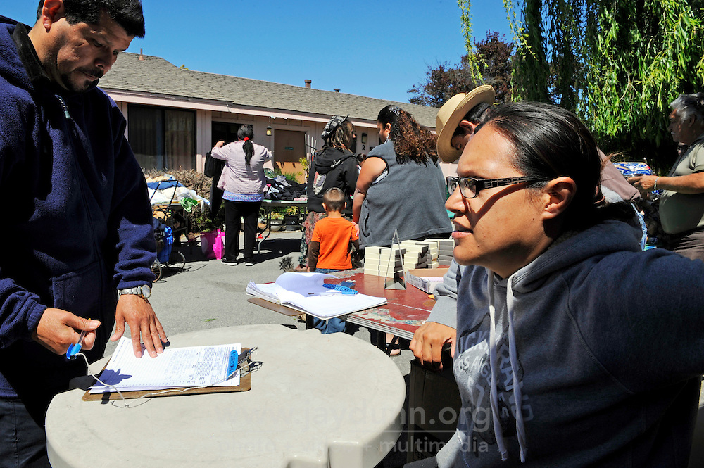 Socorro Ruiz, a volunteer along with her family for the past 20 years, helps distribute food to Hebbron residents at St. Clare's Corner, established in Salinas by the Franciscan Workers of Junipero Serra in 1982.