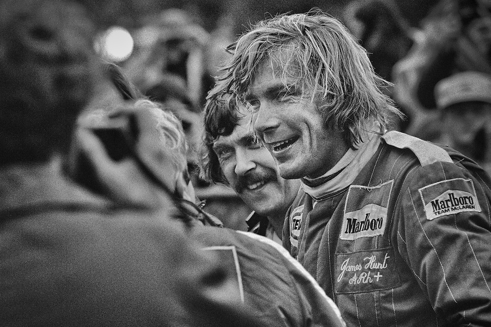 British 1976 World Champion James Hunt,  celebrates with his teammates after winning the 1977 United States Grand Prix at Watkins Glen. There might not be a better example of what has changed from the &quot;romantic&quot; era of the 70's to what we experience today.<br /> <br /> Talented McLaren driver James Hunt was one of the most complicated, charismatic and controversial individuals ever to compete in Formula One. He loved projecting his playboy image to the hilt and backed it up with outrageous statements, never-give-up speed on-track and a very full life off-track. <br /> <br /> A year earlier, he had been involved in one of the most dramatic episodes in the history of Formula One as he battled with two-time world Champion Niki Lauda down to the final race in Japan for the 1976 World Driver's Championship. <br /> <br /> That the championship was even close was due to Lauda's horrific accident that summer at the Nurburgring, were he received near fatal burns and inhaled toxic fumes...he had even received last rights of the Catholic Church. <br /> <br /> Hunt, in the meantime had won Germany and had closed up on Lauda's points lead. Miraculously, Lauda fought back and six weeks later, he returned to his Ferrari 312T at the Italian Grand Prix where he finished an incredible fourth. They arrived in Japan with Lauda ahead by three points. <br /> <br /> Hunt would win the title by a single point only after Lauda retired from the rain-soaked race because he felt conditions were too dangerous. The fire had destroyed Lauda's tear ducts and he couldn't see in the spray. <br /> <br /> Hunt and Lauda were close friends and the championship battle only strengthened their relationship.