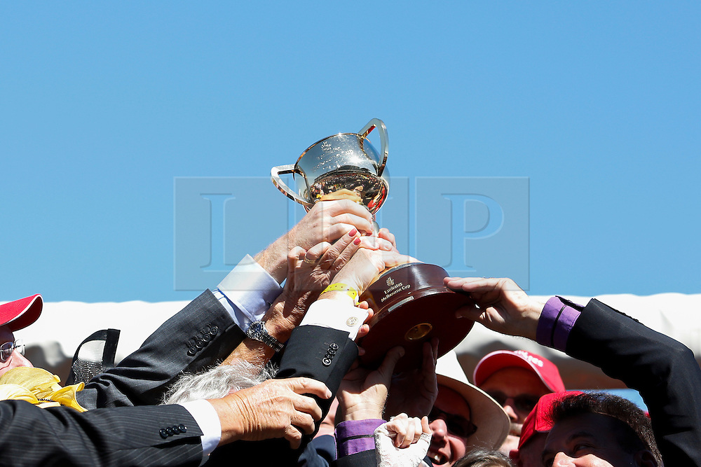 © Licensed to London News Pictures. 5/11/2013. Part owners of Fiorente hold up the Melbourne Cup after winning race 7 The Emirates Melbourne Cup during Melbourne Cup Day at Flemington Racecourse on November 5, 2013 in Melbourne, Australia. Photo credit : Asanka Brendon Ratnayake/LNP