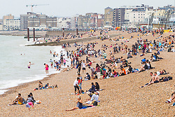 © Licensed to London News Pictures. 04/08/2019. Brighton, UK. Only a  handfuls of visitors can be seen enjoying the warm weather on the beach in Brighton as grey clouds are hanging over the seaside resort. Photo credit: Hugo Michiels/LNP