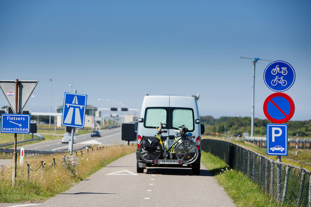 Een camper rijdt met fietsers achterop over een fietspad over de Afsluitdijk op weg naar de parkeerplaats. In 1932 werd de opening tussen de Waddenzee en de toenmalige Zuiderzee gesloten. Nu is het een belangrijke verkeersader tussen Friesland en Noord-Holland en scheidt het de Waddenzee met het IJsselmeer.<br /> <br /> A camper with bicycles at the backside is riding on a bicycle path at the Afsluitdijk. In 1932, the gap between the Wadden Sea and the former Zuiderzee closed by the Afsluitdijk. Now it is a major thoroughfare between Friesland and North Holland and it separates the Wadden Sea from the IJsselmeer.
