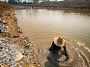 "01 APRIL 2016 - WANG NUEA, LAMPANG, THAILAND:  A man pans for gold in the Mae Wang. Villagers in the Wang Nuea district of Lampang province found gold in the Mae Wang (Wang River) in 2011 after excavation crews dug out sand for a construction project. A subsequent Thai government survey of the river showed ""a fair amount of gold ore,"" but not enough gold to justify commercial mining. Now every year when the river level drops farmers from the district come to the river to pan for gold. Some have been able to add to their family income by 2,000 to 3,000 Baht (about $65 to $100 US) every month. The gold miners work the river bed starting in mid-February and finish up by mid-May depending on the weather. They stop panning when the river level rises from the rains. This year the Thai government is predicting a serious drought which may allow miners to work longer into the summer. The 2016 drought has lowered the water level so much that the river is dry in most places and people can only pan for gold in a very short stretch of the river.     PHOTO BY JACK KURTZ"