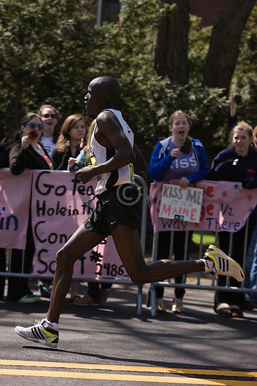 runner at midpoint in race passing spectators at Wellesley College
