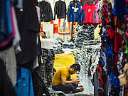12 JANUARY 2017 - BANGKOK, THAILAND:  A shopkeeper in Bo Bae Market checks his smart phone while he waits for customers. Bo Bae Market is a sprawling wholesale clothing market in Bangkok. There are reportedly more than 1,200 stalls selling clothes made in Thailand and neighboring countries. Bangkok officials have threatened to shut down parts of Bo Bae market, but so far it has escaped the fate of the other street markets that have been shut down.       PHOTO BY JACK KURTZ
