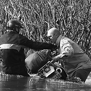 """Americans Steve Christiansen (L) and Billy Fritz attempt to ferry a motorbike across the Senphen tributary of the Bangphai River, outside the """"bomb village"""" of Ban Senphen. The village is located in the Ban Phanhop valley, one of the """"chokes"""", or narrow corridors along the Ho Chi Minh Trail in Laos that were heavily bombed by American forces during the Vietnam War."""
