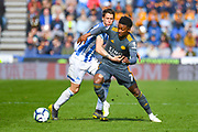 Demarai Gray of Leicester City (7) and Eric Durm of Huddersfield Town (37) in action during the Premier League match between Huddersfield Town and Leicester City at the John Smiths Stadium, Huddersfield, England on 6 April 2019.