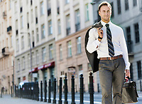 Portrait of mature businessman walking on pavement after work