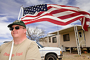 02 APRIL 2006 - THREE POINTS, AZ:  Mark Mothersead, a member of the Minuteman Project from Gilbert, AZ, carries an American flag at the Minuteman Project action between Three Points, AZ, and Sasabe, AZ, about 50 miles south of Tucson, AZ, April 2, 2006. Volunteers from the Minuteman Project have set up a line of about 20 observation posts on King's Anvil Ranch, a cattle ranch in the area.  PHOTO BY JACK KURTZ