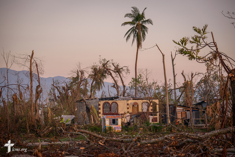 A small home and shop are framed by destruction caused by Hurricane Matthew on Wednesday, Oct. 12, 2016, in Les Cayes, Haiti. LCMS Communications/Erik M. Lunsford