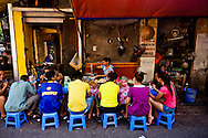 Crowd sit along a local beef noodle restaurant near Dong Xuan Market, Hanoi, Vietnam, Southeast Asia