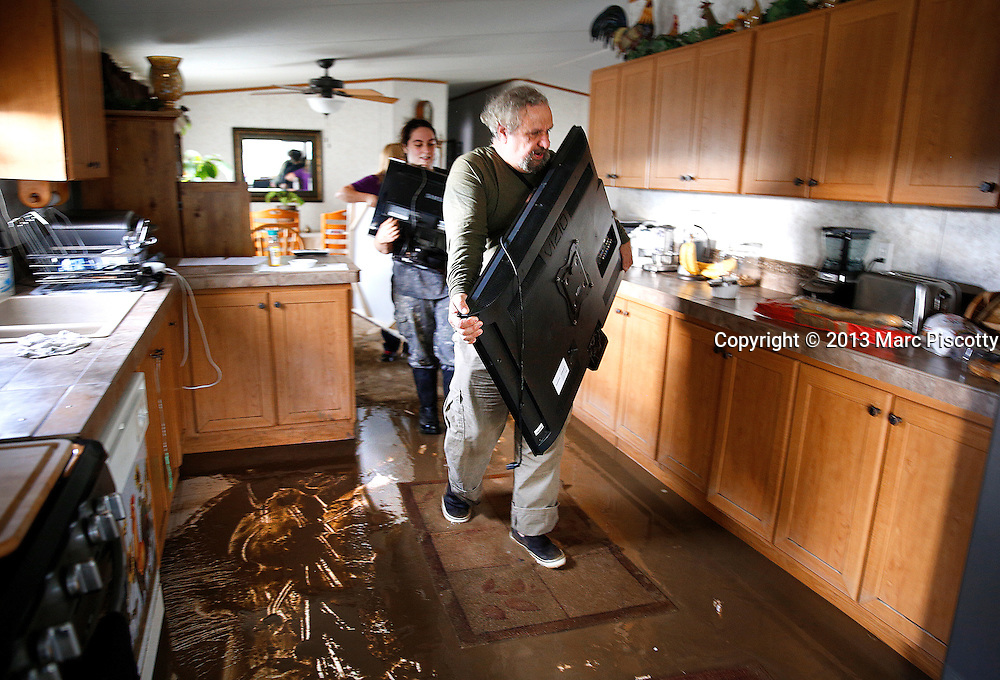 "LA SALLE, CO - SEPTEMBER 14: Don DeGraff and his niece Julie DeGraff, both of La Salle, Colorado, carry valuable items out of their home after heavy rains fueled widespread flooding in numerous Colorado towns on September 14, 2013. Don said he already plans to rebuild adding, ""we built it from nothing and we'll do it again."" (Photo by Marc Piscotty/ © 2013)"