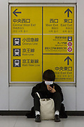A young man, wearing a paper surgical mask, sits on the floor to check his phone in Shinjuku station, Shinjuku, Tokyo, Japan. Tuesday February 4th 2020