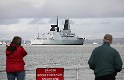 © Licensed to London News Pictures. 28/02/2014. Portsmouth, UK. People watch as the Royal Navy  Type 45 destroyer, HMS Daring arrives back in  her home port of Portsmouth today, 28th February 2014, following a 9 month trip. The trip included being diverted to help people in the Philippines following the devastation caused by Typhoon Haiyan. Photo credit : Rob Arnold/LNP