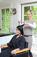 Cheerful hairstylist giving a haircut to beautiful mid adult woman in beauty salon