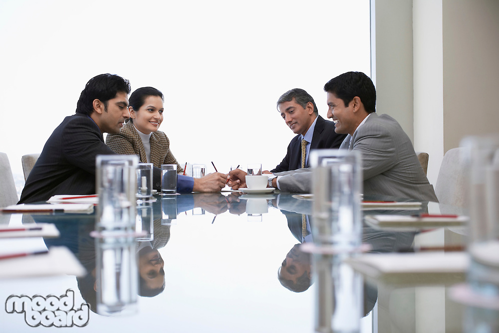 Small corporate business meeting viewed along reflective surface of conference table