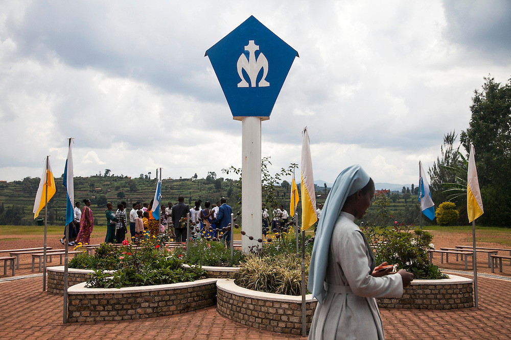 A nun walks by people gathering around a Virgin Mary statue (on the other side of blue and white pole) at the Shrine of Our Lady of Sorrows in Kibeho, Rwanda. This is the only sanctioned Marian sanctuary in Africa. Kibeho's overseers and the Rwandan government hope this place will become a top tourism site. This statue marks one of the spots where three young Rwandan women had visions of Mary. The very first vision came to Alphonsine Mumureke, then 16, on Nov. 28, 1981.<br /> <br /> Photographed on Sunday, October 26, 2014.<br /> <br /> Photo by Laura Elizabeth Pohl