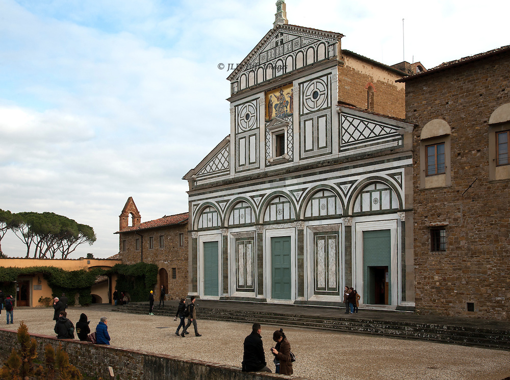 Visitors strolling and sitting in the plaza before the church of San Miniato del Monte.  At left, single story structure is the pharmacy in which the Olivetan (Benedictine) monks sell herbal preparations that they have made.