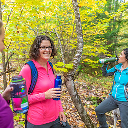 Three women take a break during a hike in the Raymond Community Forest in Raymond, Maine. Fall.