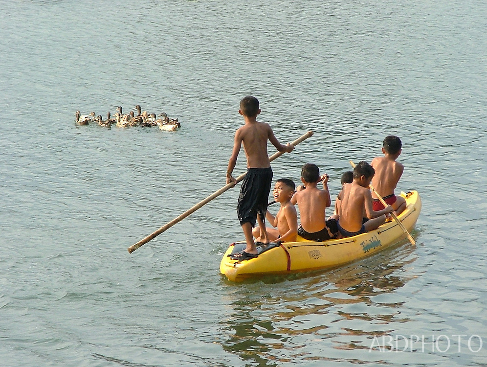 Children in boat chasing ducks Vang Vieng Laos