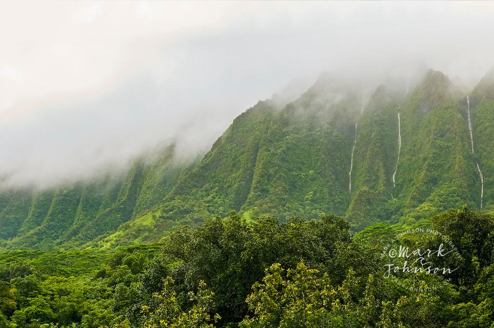 Waterfalls cascade down the vertical cliffs of the Koolau Mountains, Oahu, Hawaii