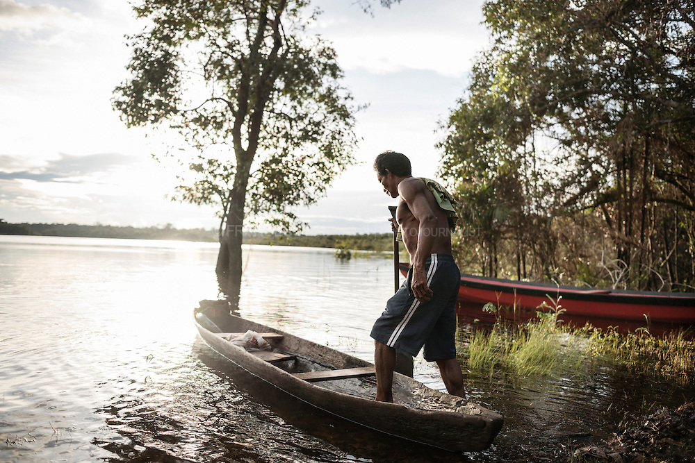 """A Mawe moves from village to village using a traditional canoe. Guarana is a plant native to the highlands of the Maues River basin, which coincides precisely with the Satere-Mawe's traditional territory. The Satere-Mawe have transformed the """"Paullinia cupana"""", a wild vine of the Sapindacea family, into a cultivated shrub, and mastered its planting and processing."""