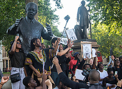 London, July 8th 2016. Hundreds gather on London's Southbank before marching through the streets of London to Parliament Square, Downing Street and the BBC, in a Black Lives Matter protest in solidarity with Americans following the shooting dead of two black men, Philando Castile in Minnesota and Alton Sterling in Louisiana by police in the US. PICTURED: Gathered round the statue of Nelson Mandela, the crowd prepares to march on Downing Street.
