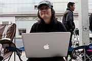 Fuiushiko Ikeda uses his Apple mac laptop computer as he waits in line with at the Apple store awaiting the official release of the iphone4S in Ginza, Tokyo, Japan. Friday October 14th 2011. The latest version of the popular iphone was released worldwide on October 14th. Japans flagship Apple store in Ginza was opened at 8am for the 800 people that had been waiting to be the first to purchase the new telephone.