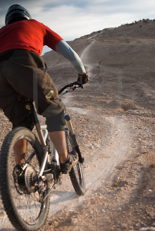 the white mesa bike trails are a designated mountain biking area near the small town of san ysidro, new mexico, 40 miles from albuquerque.  rider kevin lange charges the perfect desert singletrack of the dragon's back.  self portrait.