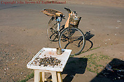 Snails are available as street food near a bicycle used by a vendor to sell them on a city street in Kampong Cham, Cambodia.