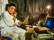 15 OCTOBER 2015 - BANGKOK, THAILAND:  A Chinese opera performer checks his email while he puts on his make up before performing at the Vegetarian Festival at the Joe Sue Kung Shrine in the Talat Noi neighborhood of Bangkok. The Vegetarian Festival is celebrated throughout Thailand. It is the Thai version of the The Nine Emperor Gods Festival, a nine-day Taoist celebration beginning on the eve of 9th lunar month of the Chinese calendar. During a period of nine days, those who are participating in the festival dress all in white and abstain from eating meat, poultry, seafood, and dairy products. Vendors and proprietors of restaurants indicate that vegetarian food is for sale by putting a yellow flag out with Thai characters for meatless written on it in red. The shrine is famous for the Chinese opera it hosts during the Vegetarian Festival. The operas are free.   PHOTO BY JACK KURTZ
