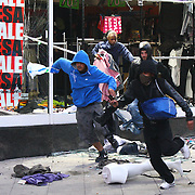 Rioters run from police after looting as shop in Peckham during the 2011 August riots in London
