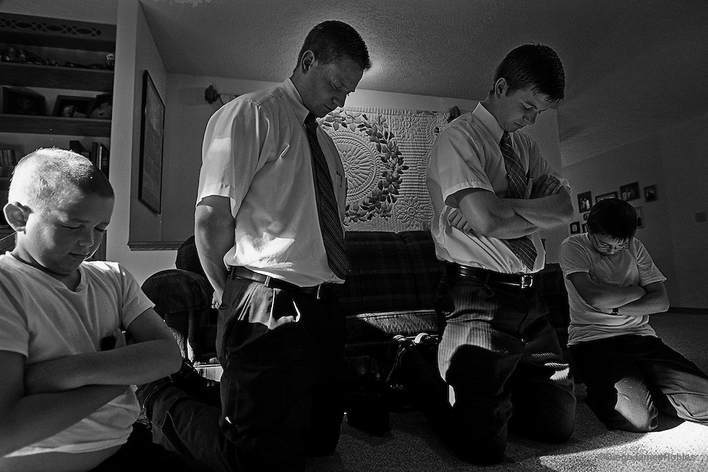 Church members, (left) Abe Ogle, 10, and his brother Sam Ogle, 12, pray with Mormon missionaries, (left) Elder Bradley Merrill and Elder Todd Balls after dinner, in Athens, Ohio, on Sunday, May 25, 2008. Followers of the Church of Jesus Christ of Latter-day Saints often invite missionaries into their homes to review doctrine and help them offset the cost of their mission with free meals.