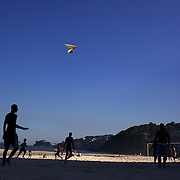 Locals play beach football during the late afternoon sunshine at Sao Conrado beach as a hang glider prepares to land on the beach, Rio de Janeiro,  Brazil. 8th July 2010. Photo Tim Clayton...