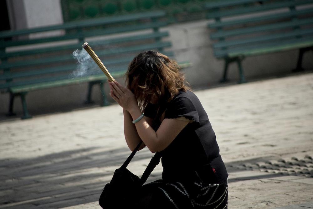 Dans la seconde cour en face du grand hall d'assemblée une femme effectue sa prière en se tournant vers les trois temples dédiés au bouddha.