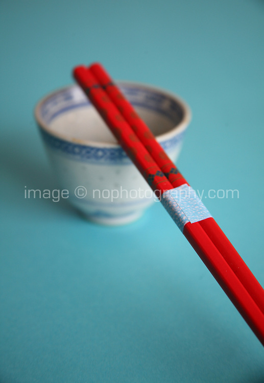 Red wooden chopsticks resting across china cup with blue background