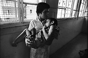 Beirut, Lebanon June 14th 1982. Sabra palestinian refugees camp. Sabra psychiatric hospital . A girl holds a sick and starving child in her harms during the evacuation of  the frequently targetted Hospital since the beggining of the Israeli offensive. ©Herve Merliac